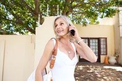 Femme plus âgée heureuse marchant dehors avec le téléphone portable Photographie stock