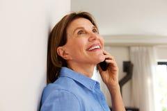 Femme plus âgée heureuse parlant au téléphone portable à la maison images stock