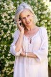 Femme plus âgée heureuse parlant au téléphone portable Images stock