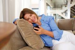 Femme plus âgée heureuse s'asseyant sur le sofa regardant le téléphone portable image stock