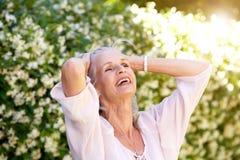 Femme plus âgée insouciante avec des mains dans les cheveux Photo libre de droits