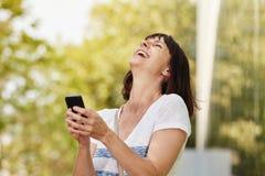 Femme plus âgée riante tenant le téléphone intelligent dehors photographie stock libre de droits
