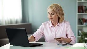 Femme plus de 50 données entrantes de sa carte, payant des services de service en ligne photos stock