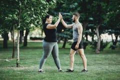 Femme plus de taille secouant le bras de l'entraîneur personnel image stock