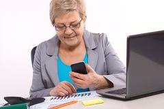 Femme pluse âgé d'affaires à l'aide du téléphone portable et travaillant à son bureau dans le bureau, concept d'affaires Image stock