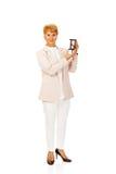 Femme pluse âgé d'affaires de sourire tenant des sandglass Photographie stock