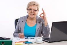 Femme pluse âgé d'affaires montrant le signe correct et travaillant à son bureau dans le bureau, concept d'affaires image libre de droits