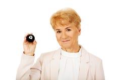 Femme pluse âgé heureuse d'affaires tenant la billard-boule huit Photographie stock libre de droits