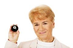 Femme pluse âgé heureuse d'affaires tenant la billard-boule huit Image stock