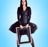 Femme portant dans la robe noire tenant le cadre de tableau Image libre de droits