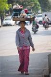 Femme portant fortement sur sa tête image stock