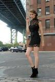 Femme portant la mini-robe noire se tenant sous le pont de Manhattan Image libre de droits