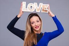 Femme portant la robe bleue tenant le symbole d'amour de signe Photographie stock libre de droits