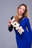 Femme portant la robe bleue tenant le symbole d'amour de signe Image stock