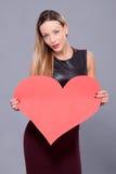 Femme portant la robe noire tenant le grand symbole d'amour de signe de coeur Photo libre de droits
