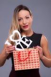 Femme portant la robe noire tenant le symbole d'amour de signe Image stock