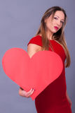 Femme portant la robe rouge tenant le grand symbole d'amour de signe de coeur Photo stock