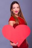 Femme portant la robe rouge tenant le grand symbole d'amour de signe de coeur Photographie stock