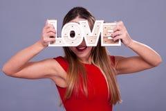 Femme portant la robe rouge tenant le symbole d'amour de signe Images stock