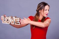 Femme portant la robe rouge tenant le symbole d'amour de signe Images libres de droits