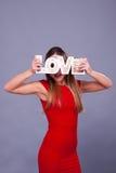 Femme portant la robe rouge tenant le symbole d'amour de signe Photographie stock libre de droits