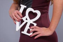 Femme portant la robe rouge tenant le symbole d'amour de signe Image libre de droits