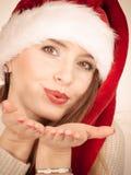 Femme portant le baiser de soufflement de chapeau du père noël Images stock