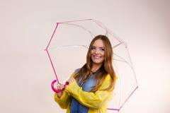 Femme portant le manteau imperméable sous le parapluie Photo libre de droits