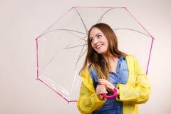 Femme portant le manteau imperméable sous le parapluie Photo stock