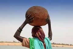 Femme portant un bac Photographie stock libre de droits