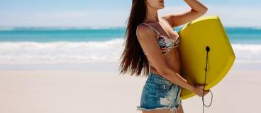 Femme portant un bodyboard à la plage photographie stock