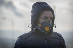 Femme portant un vrai masque protecteur contre la pollution, d'anti-brouillard enfumé et de virus images libres de droits