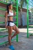 Femme posant à côté des barres horizontales de sports image libre de droits
