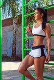 Femme posant à côté des barres horizontales de sports images stock