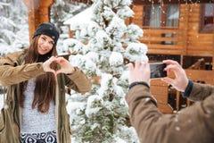 Femme posant à l'ami prenant des photos de elle avec le smartphone Photographie stock libre de droits