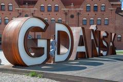 Femme posant aux lettres célèbres et rouillées en métal de Danzig, Pologne images stock