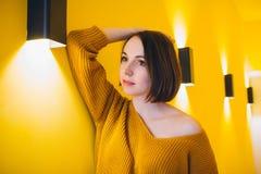Femme posant contre le mur jaune Image stock