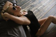 Femme posant près du lit et tenant ses mains derrière sa tête Photographie stock