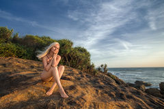 Femme posant sur la roche dans l'océan Photo libre de droits