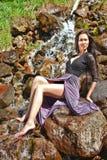 Femme posant sur les roches par la rivière Photographie stock