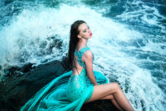 Femme posant sur une plage avec des roches Photo stock