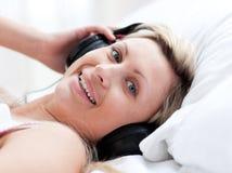 Femme positif avec des écouteurs sur se trouver sur un bâti Images stock