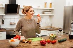 Femme positive avec les cheveux attachés observant la tomate dans sa main photo libre de droits