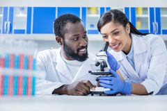 Femme positive avec plaisir à l'aide d'un microscope image stock