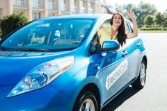 Femme positive avec plaisir se penchant hors de la fenêtre de voiture Photos libres de droits