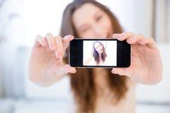 Femme positive espiègle clignant de l'oeil et prenant le selfie avec le smartphone Photos libres de droits