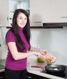 Femme positive faisant frire des crevettes Photographie stock libre de droits