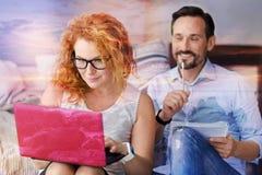 Femme positive futée travaillant sur un ordinateur portable à côté de son ami intelligent Photos libres de droits