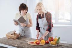 Femme positive heureuse préparant une salade Photographie stock