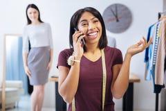 Femme positive parlant au téléphone tandis que son attente de client Photographie stock libre de droits